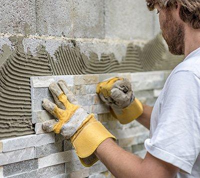 Man Setting Tile on Wall