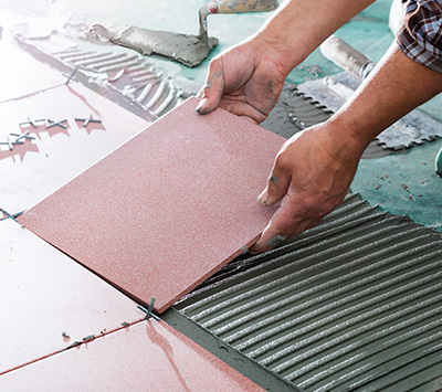 Man Placing Pink Tile Over the Floor